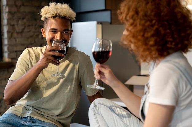 彼らの新しい家の台所で一緒にワインを持っているカップル