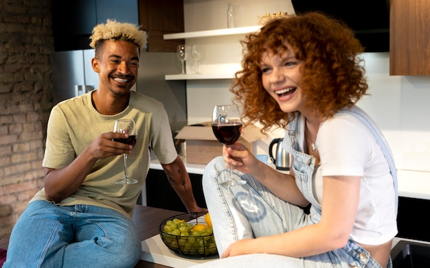 Couple having wine together in the kitchen of their new home