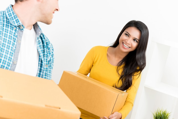 Couple helping eaching other moving into new house