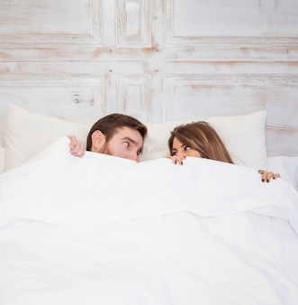 Couple hiding under blanket on bed