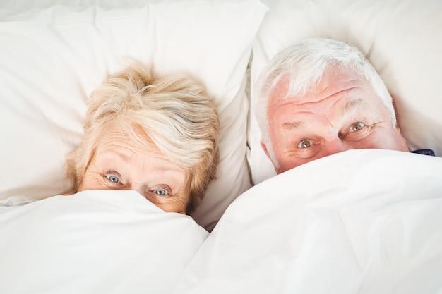 Couple hiding in blanket