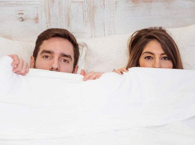 Couple hiding under white blanket on bed