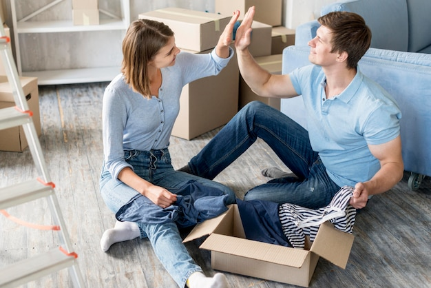 Пара приветствует друг друга, собирая вещи для переезда