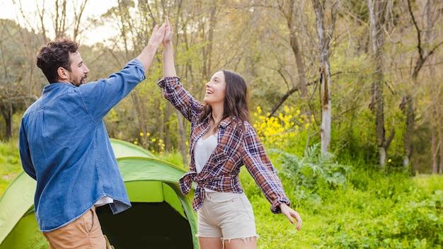 Пара высокой прыжков возле палатки