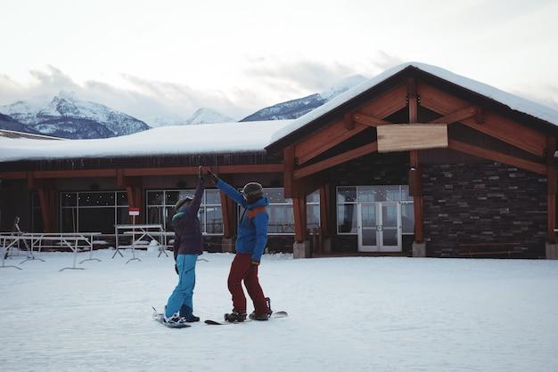 Coppia alta fiving sul campo coperto di neve