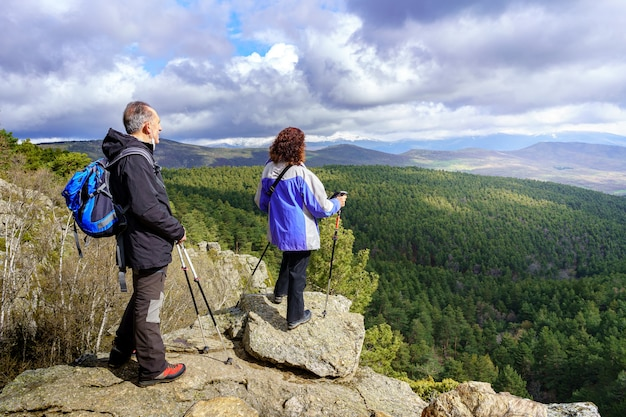 Couple of hikers contemplating the landscape from the top of the mountain