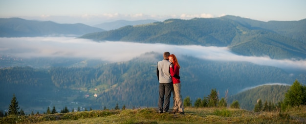 Couple hikers hugging and enjoying beautiful mountain landscape with morning haze over the mountains and forests. panorama