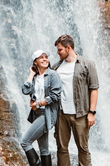 Couple hikers tourists looking at waterfall copy space