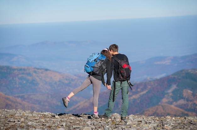 Couple hikers with backpacks on the ridge of the mountain
