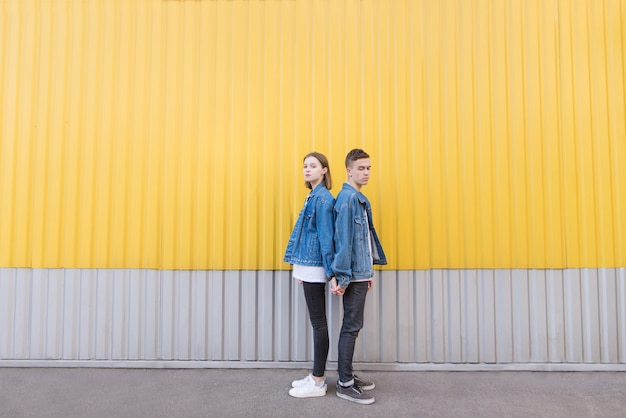 Couple of hipsters in denim jackets poses against background of wall