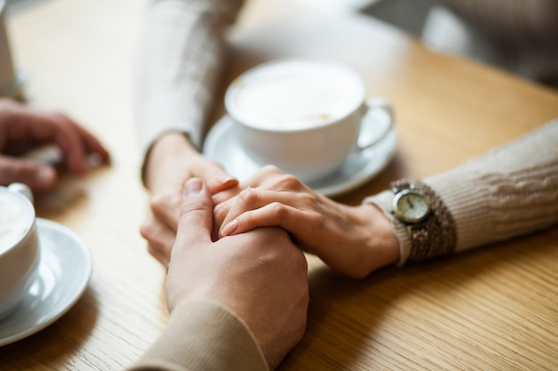 Couple hold hands drinking coffee in cafe