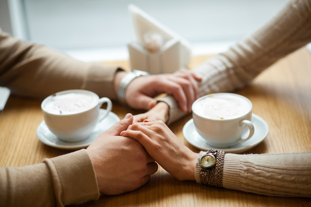Couple hold hands drinking coffee in cafe,