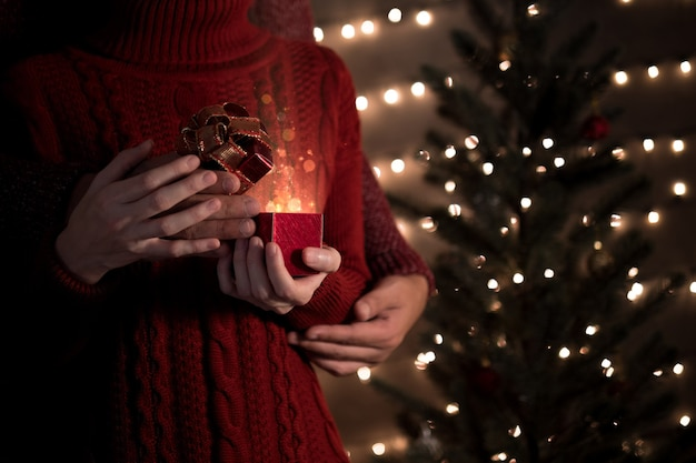 Couple hold and open a red christmas gift box with magical lights