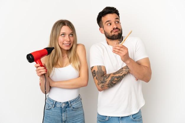 ヘアドライヤーを保持し、孤立した白い背景の上に歯を磨くカップルは、肩を持ち上げながらジェスチャーを疑う