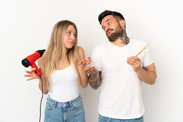 ヘアドライヤーを保持し、孤立した白い背景の上に歯を磨くカップルは、肩を持ち上げながら重要でないジェスチャーをします