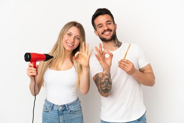 ヘアドライヤーを保持し、指でokサインを示す孤立した白い背景の上に歯を磨くカップル