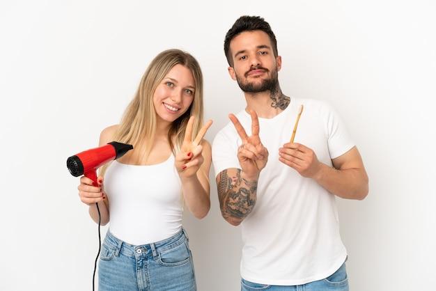ヘアドライヤーを保持し、笑顔で勝利のサインを示す孤立した白い背景の上に歯を磨くカップル
