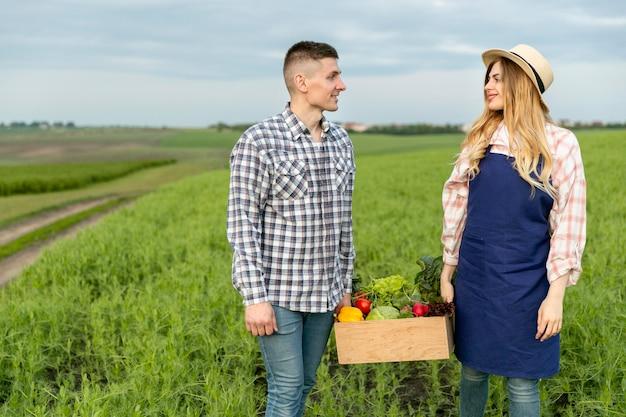 Couple holding basket of vegetables