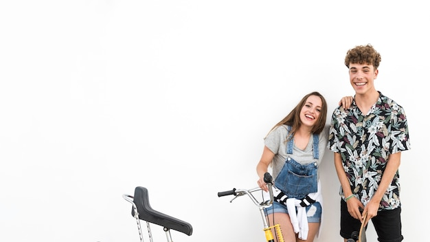 Couple holding bicycle and skateboard against white background