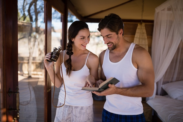 Couple holding binoculars while reading novel during safari vacation