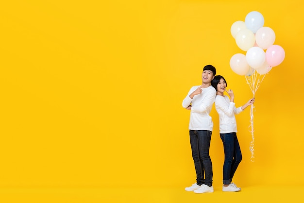 Couple holding bunch of balloons