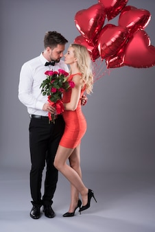 Couple holding a bunch of flowers and balloons