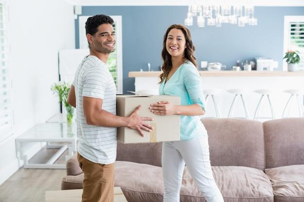 Пара, держа карточные коробки в гостиной дома
