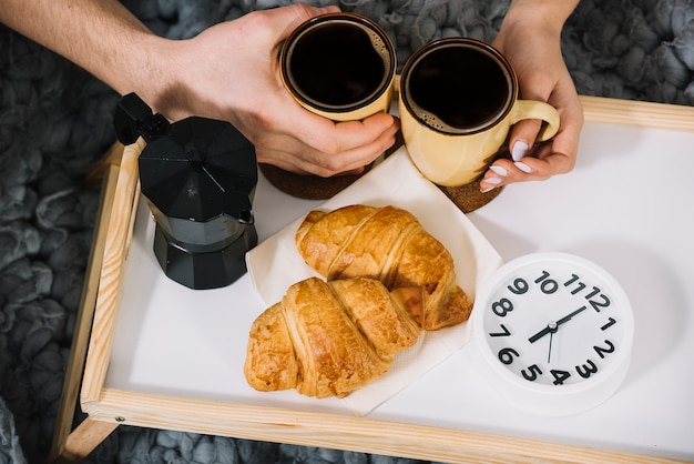 Couple holding coffee cups on tray