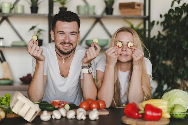 Fette del cetriolo della tenuta delle coppie che stanno dietro il contatore di cucina