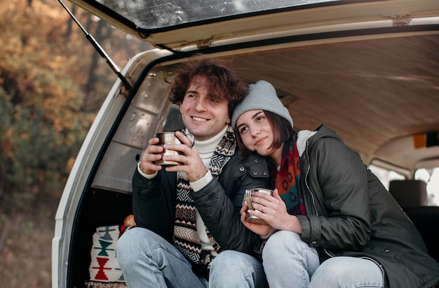 Couple holding cups of coffee in a van