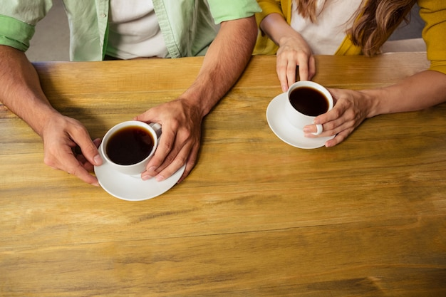 Couple holding cups of coffee