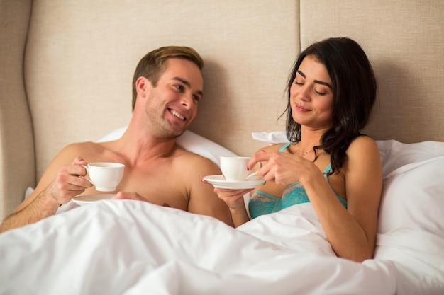 Пара, держащая чашки в постели.