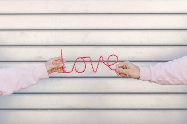 Couple holding decorative love sign