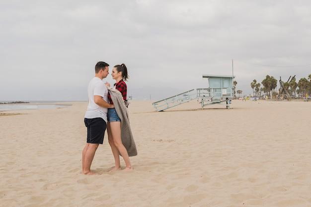 Пара, держа друг друга на пляже и позирует