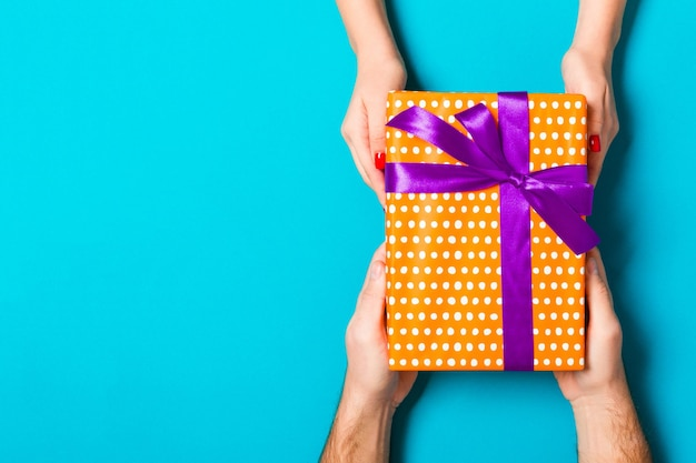 Couple holding a gift box on blue. flat lay