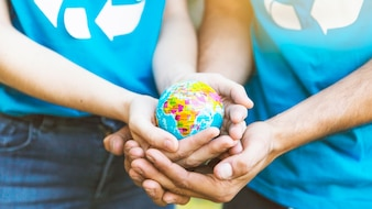 Couple holding globe in hands together