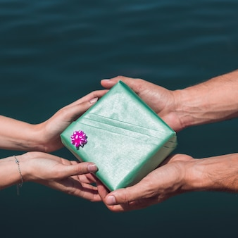Couple holding green gift box in front of sea water background
