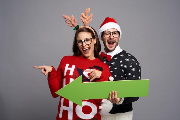 Couple holding a green screen arrow