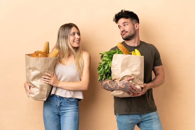 Couple holding grocery shopping bags over isolated background looking over the shoulder with a smile