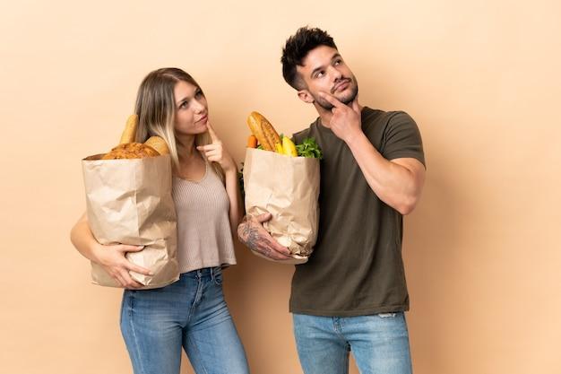 Пара, держащая сумки для покупок, размышляя над идеей, глядя вверх