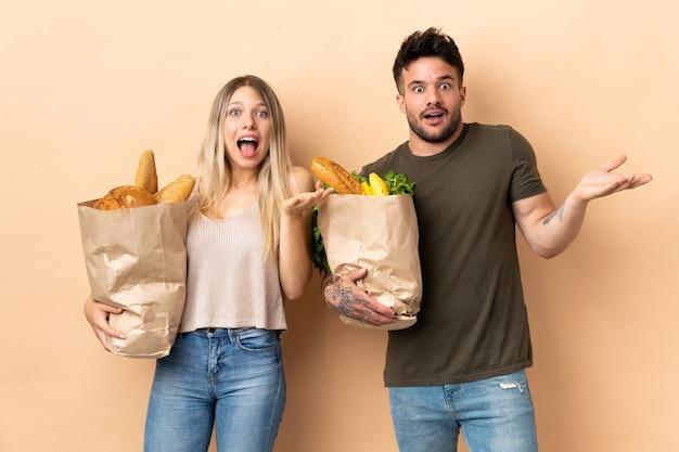 食料品の買い物袋を持っているカップル