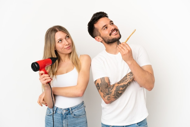 Couple holding a hairdryer and brushing teeth over isolated white background looking up while smiling