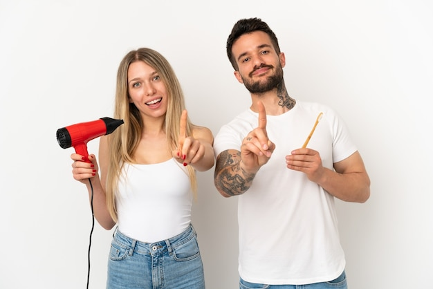 Couple holding a hairdryer and brushing teeth over isolated white background showing and lifting a finger
