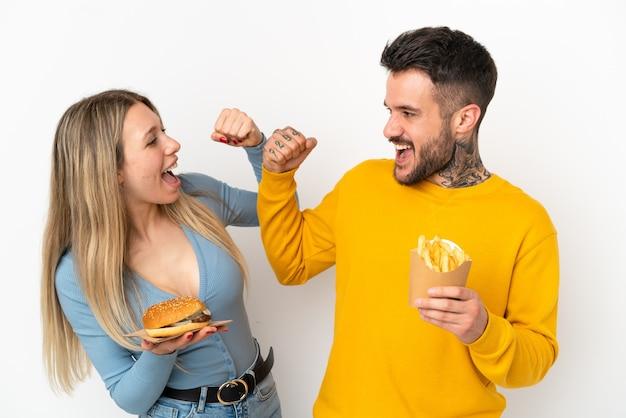 Пара, держащая гамбургер и жареные чипсы на изолированном белом фоне, празднует победу в позиции победителя