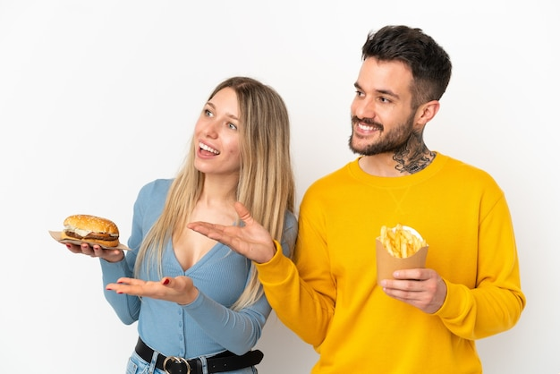 Пара, держащая гамбургер и жареные чипсы на изолированном белом фоне, указывая назад и представляя продукт