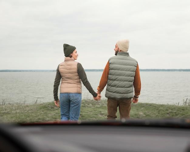 自然の中で車の前で手をつないでカップル