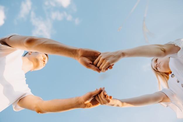 青い空の背景に手をつないでカップル。