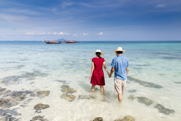 Couple holding hand walking in to crystal clear sea with long tail boat