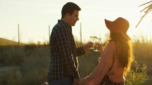 手をつないで、日没時に白ワインを味わうカップル。
