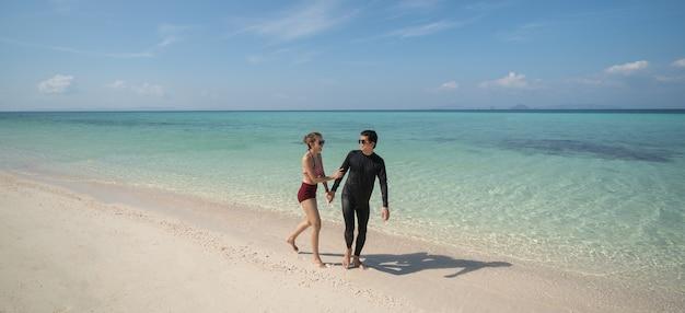 手をつないで、美しい夏休みを楽しんでビーチを歩くカップル。旅行休暇のライフスタイルの概念